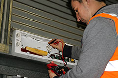 MFE electrician checking exit light